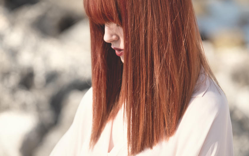 Side profile of a woman in a white top with mid-length straight hair in muted red tones