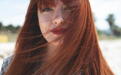 Close-up of a woman with mid-length straight hair in muted red tones