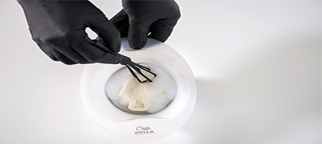 A small white bowl filled with creamy liquid, being mixed with a small brush held in black-gloved hands