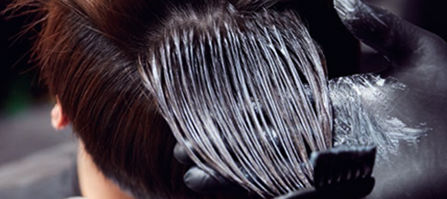 A black-gloved hand holds strands of a woman's short, dark hair and brushes it with color solution