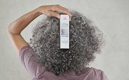 вид сзади женской головы с текстурированными седыми волосами; женщина держит упаковку True Grey Wella Professionals