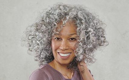 улыбающаяся женщина с натуральными седыми волосами, обработанными тонером True Grey от Wella Professionals